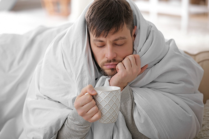 Man in bed with bronchitis